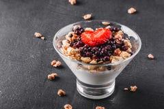 Очень вкусный granola с йогуртом, свежими ягодами, клубникой в стекле на черной предпосылке Здоровые ингридиенты завтрака стоковое фото