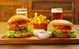 2 очень вкусных гамбургера с говядиной, луком, томатом, салатом и сыром с кетчуп, мустардом и 2 стеклами пива дальше Стоковое Изображение RF