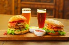 2 очень вкусных гамбургера с говядиной, луком, томатом, салатом и сыром с кетчуп, мустардом и 2 стеклами пива дальше Стоковые Изображения RF