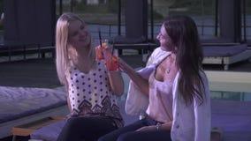 2 очень вкусных девушки выпивая коктейли в клубе 2 усмехаясь девушки clink стекла с коктейлями и сидеть болтовни видеоматериал
