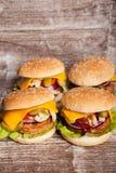 4 очень вкусных домашних сделанных бургера на деревянной плите Стоковое фото RF