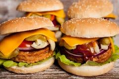 4 очень вкусных домашних сделанных бургера на деревянной плите Стоковая Фотография