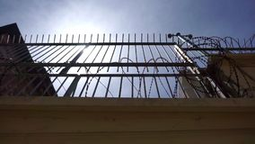 Очень высокая загородка тюрьмы, со стальными прутами и острой колючей проволокой видеоматериал