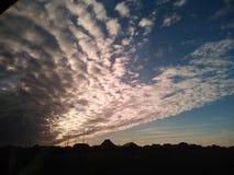 Очень интересные облака над силуэтами старой деревни стоковое фото rf