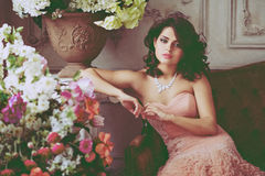 Очень красивое брюнет девушки в розовом платье сидя на кресле Стоковое Изображение RF