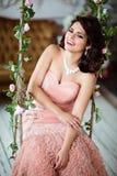 Очень красивое брюнет девушки в розовый смеяться над платья, сидя дальше Стоковые Фото