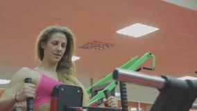 Очень красивый женский тренер тренирует на тренажере в фитнес-клубе акции видеоматериалы