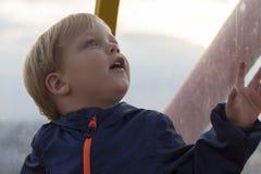 Очень милый удивленный мальчик Смешная сторона мальчика смотря вверх против запачканной предпосылки стоковые фото