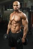 Очень приведите атлетического парня в действие стоя в спортзале с гантелями и lokking на камере Стоковые Изображения