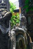 Очень старая скульптура камня дракона покрытая с мхом и лишайниками в Бали, Индонезии стоковые фото