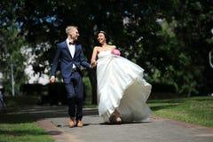 Очень счастливые пары новобрачных идут в парк Стоковые Изображения RF