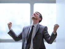 Очень счастливый бизнесмен стоя в офисе Фото с космосом экземпляра стоковое фото rf