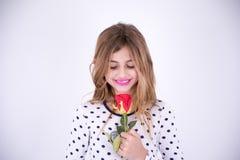 Очень счастливая девушка смотря красный цветок Стоковое Изображение RF