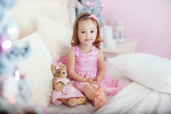 Очень славная очаровательная блондинка маленькой девочки в розовом платье сидя на кровати и смехе ` s ребенка громко предпосылка  стоковое фото rf