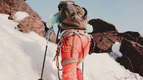 Очень хорошая натренированная группа в составе альпинисты с их оборудованием пробуя взобраться очень крутой, снежный наклон горы сток-видео