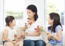 2 дочери вручая гвоздики матери Стоковые Изображения