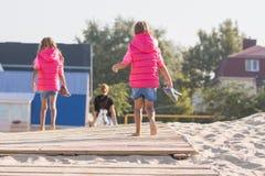 2 дочери идут домой для его матери на деревянном настиле в песке Стоковые Фото