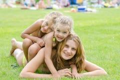 2 дочери счастливо сидят на маме задней, горячем летнем дне ослабляя на зеленой лужайке Стоковая Фотография RF