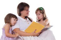 2 дочери слушая их книга чтения матери Стоковые Изображения RF