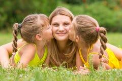 2 дочери целуя мать лежа на траве на пикнике Стоковые Изображения