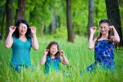 2 дочери целуя мать с обеих сторон их матери Стоковые Фотографии RF