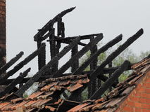 Очерненные стропилины крыши, который сгорели вниз с жилого дома после огня стоковое фото
