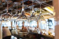 Очистите бокалы подготовленные барменом и повешенные на баре на ресторане Стоковая Фотография