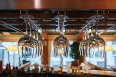 Очистите бокалы подготовленные барменом и повешенные на баре на ресторане Стоковое Фото