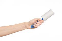 Очистите одежды и очищать тему дома: человеческая рука держа голубую липкую щетку для очищая одежд и мебель от пыли Стоковая Фотография
