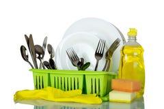Очистите плиты и столовый прибор в сушильщике, около тензида и губки изолированных на белизне Стоковые Фото