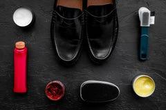 очистьте ботинки Комплект продуктов заботы ботинка Заполированность, щетки, воск, губка Черное взгляд сверху предпосылки Стоковая Фотография RF