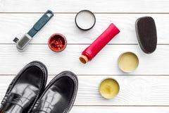 очистьте ботинки Комплект продуктов заботы ботинка Заполированность, щетки, воск, губка Белое взгляд сверху предпосылки Стоковое Изображение