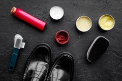 очистьте ботинки Комплект продуктов заботы ботинка Заполированность, щетки, воск, губка Черное взгляд сверху предпосылки Стоковое Фото