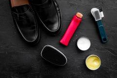 очистьте ботинки Комплект продуктов заботы ботинка Заполированность, щетки, воск, губка Черное взгляд сверху предпосылки Стоковые Изображения