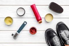 очистьте ботинки Комплект продуктов заботы ботинка Заполированность, щетки, воск, губка Белое взгляд сверху предпосылки Стоковое фото RF