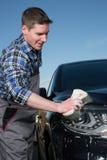 Очищать автомобиль на улице с губкой Стоковые Фото