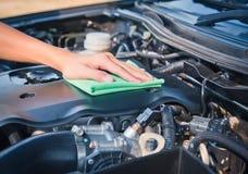 Очищать двигатель автомобиля с зеленой тканью microfiber Стоковые Фотографии RF