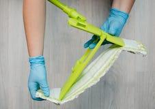 Очищать в квартире Женские руки в голубых резиновых перчатках C Стоковое Изображение