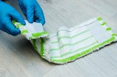 Очищать в квартире Женские руки в голубых резиновых перчатках C стоковое фото