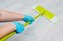 Очищать в квартире Женские руки в голубых резиновых перчатках C Стоковая Фотография RF