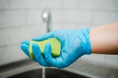 Очищать в квартире Женские руки в голубых резиновых перчатках C Стоковая Фотография