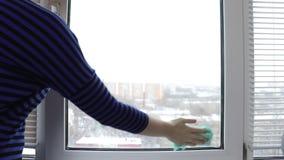 Очищать окно с брызгами мытья и сыпню молодой женщиной акции видеоматериалы