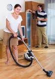 Очищать счастливой женщины вакуумируя плоско Стоковые Изображения RF