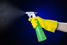 Очищать тему дома и уборщика: рука человека в желтой перчатке держа зеленую бутылку брызга для очищать на синем backgr Стоковое Изображение RF
