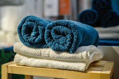 4 очищают мягкие двойные полотенца ванны установленные штабелированных других цветов, лежащ на деревянном стуле Стоковая Фотография