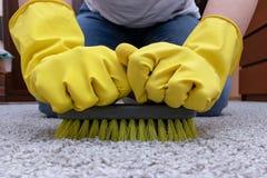Очищая ковер с щеткой, руки в желтых резиновых перчатках делая домашний режим стоковое фото rf