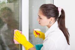 Очищая концепция Окно стирки молодой женщины стоковое изображение