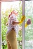 Очищая концепция Окно стирки молодой женщины стоковые фото
