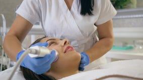 Очищая лицевая обработка, счастливая женщина клиента наслаждается процедурами по косметики rejuvenating заботы кожи в косметическ видеоматериал