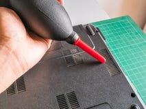 Очищая пылевоздушный вентилятор компьтер-книжки с воздуходувкой воздуха Ракеты стоковая фотография rf